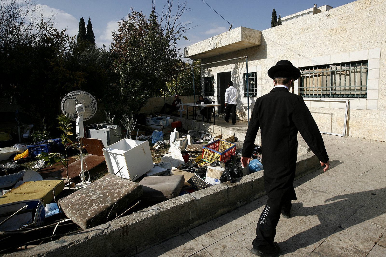 An ultra-Orthodox Jew walks past belongings thrown out from a Palestinian house in the neighborhood of Sheikh Jarrah in East Jerusalem, December 3, 2009. (Miriam Alster/Flash90)