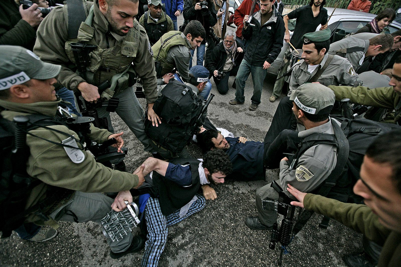 Israeli policemen detain a left-wing Israeli activist during a protest against Jewish settlers taking over homes in the Sheikh Jarrah neighborhood in East Jerusalem, December 11, 2009. (Abir Sultan/Flash90)