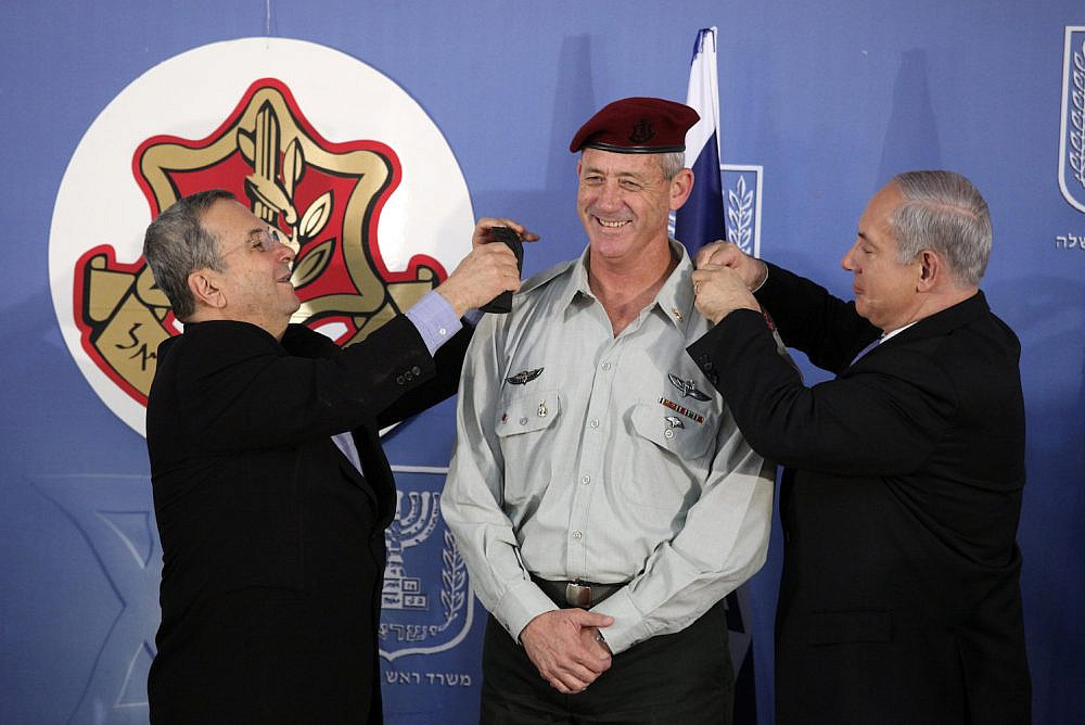 Israeli Prime Minister Benjamin Netanyahu and former Israel's Defense Minister Ehud Barak change the epaulets of Israeli Chief of Staff Benny Gantz, February 14, 2011. (Abir Sultan/Flash90)