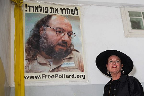 Esther Pollard, wife of convicted Israeli spy Jonathan Pollard, walks past a poster of her husband prior to speaking to press outside her home in Jerusalem, July 29, 2015. (Flash90)
