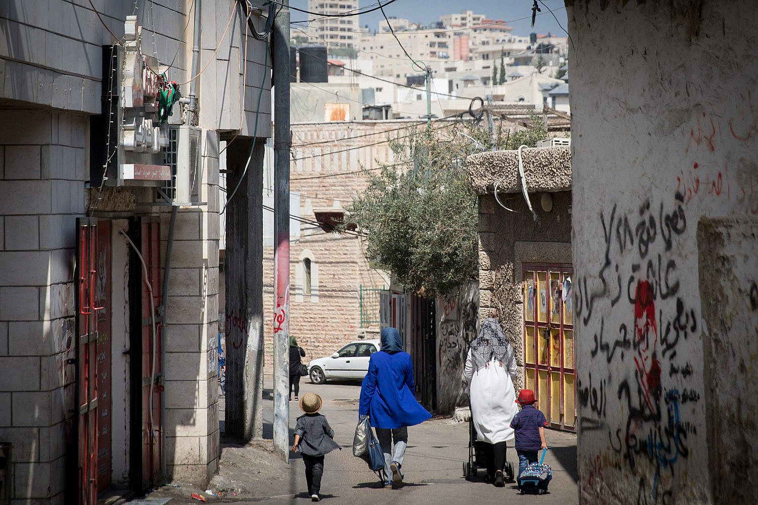 Palestinian women walk through the alleyways of Dheisheh Refugee Camp, in the West Bank city of Bethlehem, August 30, 2018. (Miriam Alster/Flas90)