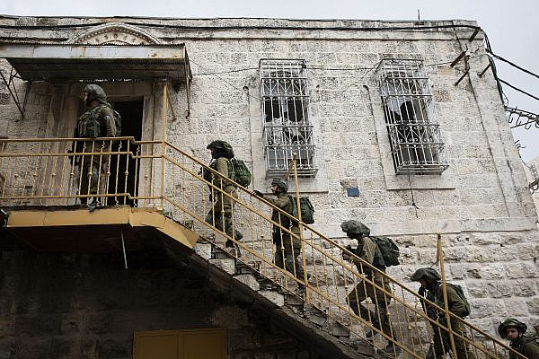 Israeli soldiers raid a Palestinian house as hundreds of demonstrators march in the West Bank city of Hebron calling to open Shuhada Street, February 20, 2019. (Activestills.org)