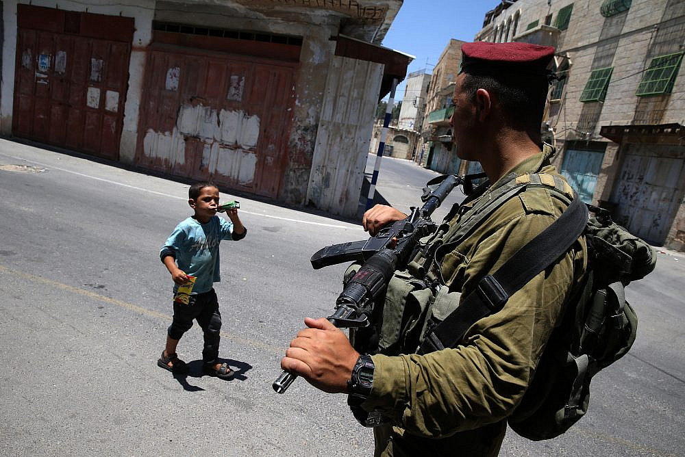 A Palestinian boy walks near Israeli soldiers in the West Bank city of Hebron, on the first Friday of the Muslim month of Ramadan. July 04, 2014. (Nati Shohat/Flash90)