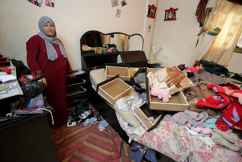 A Palestinian woman examines the damage in her house after a night raid by Israeli soldiers, Balata Refugee Camp, West Bank, January 3, 2017. (Ahmad Al-Bazz/Activestills.org)