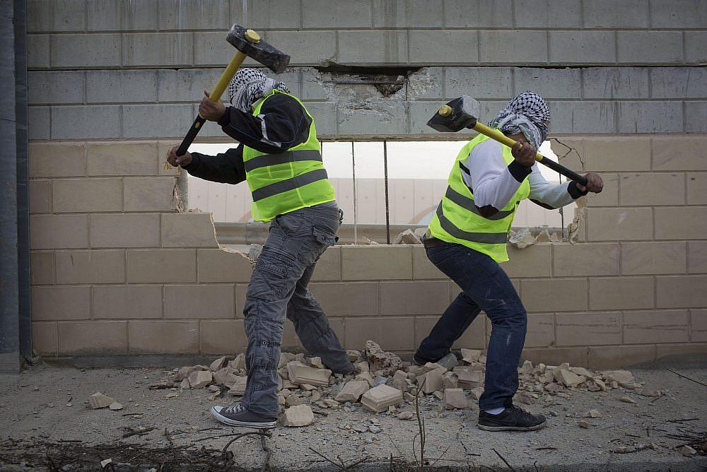 Palestinian activists destroy part of the separation wall in the West Bank village of Bir Nabala, near Ramallah, Nov. 15, 2013. (Activestills)