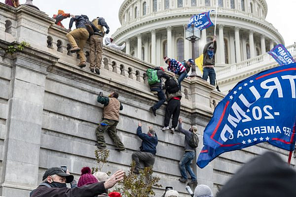 Supporters of U.S. President Donald Trump climb the wall of the Capitol, January 6, 2021. (Blink O'fanaye/CC BY-NC 2.0)