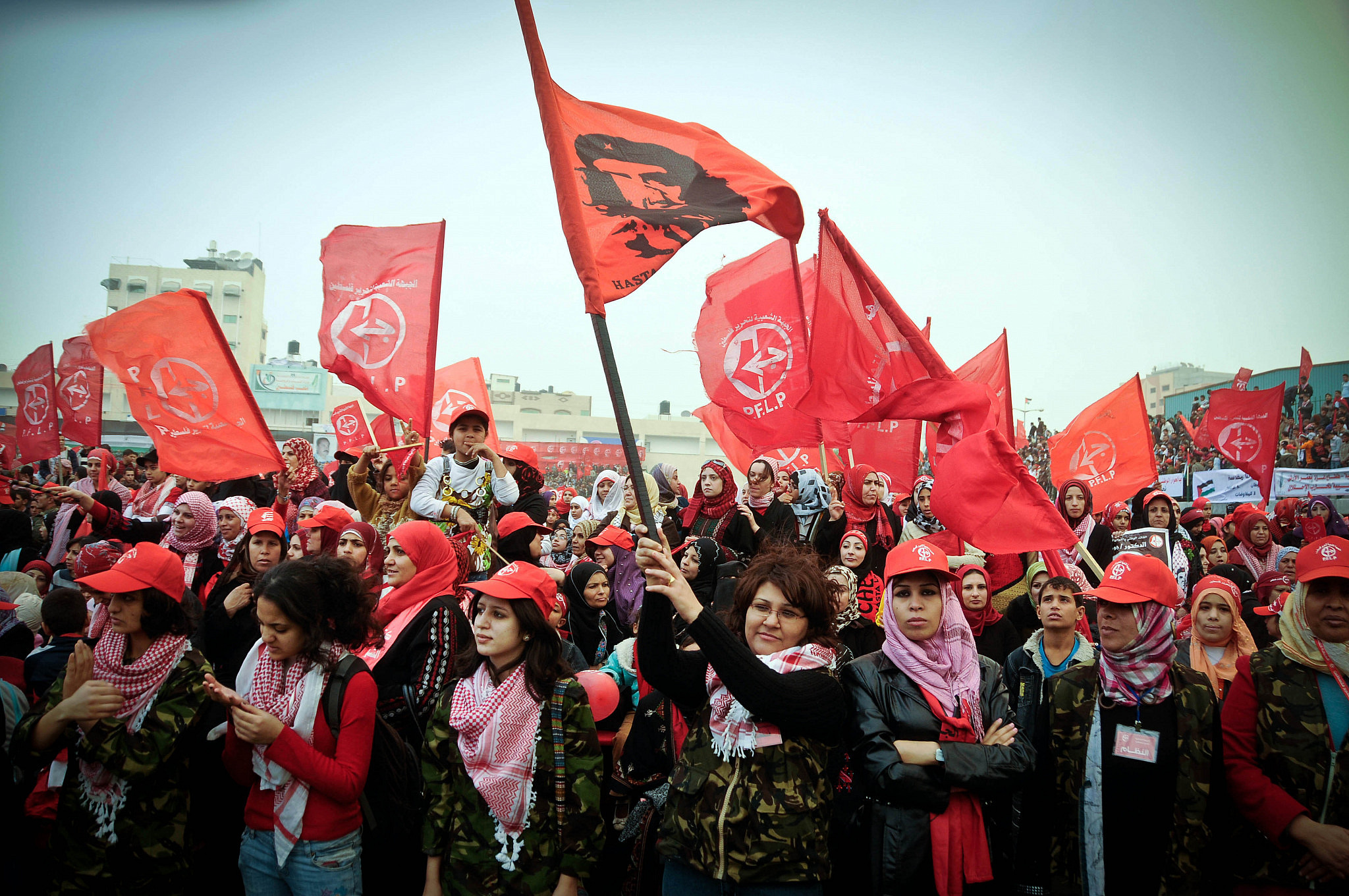 Palestinian women sing while waving red flags at a rally marking the 43rd anniversary of the leftist Popular Front for the Liberation of Palestine (PFLP), in Gaza City, Dec. 11, 2010. (Mustafa Hassona/Flash90)