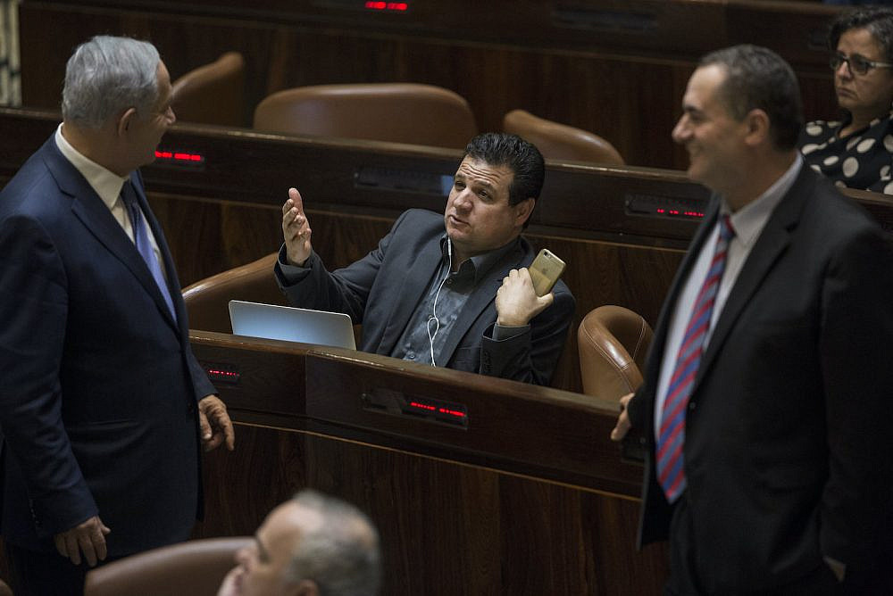 Prime Minister Benjamin Netanyahu and Joint List party chairman Ayman Odeh talk during a vote at the Knesset on November 18, 2015. (Hadas Parush/Flash90)