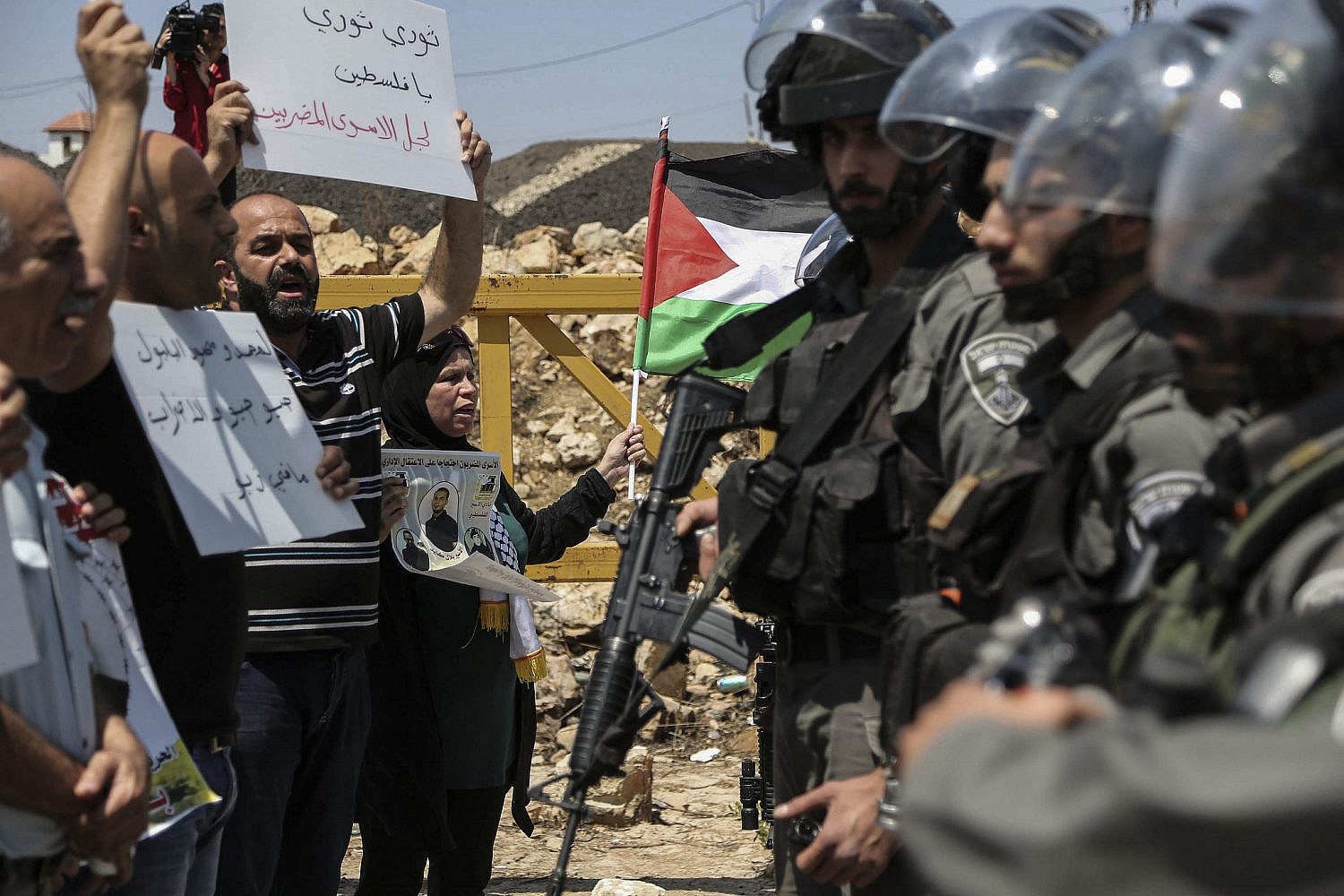 Palestinian protesters hold flags as they argue with Israeli border policemen during a protest in solidarity with Palestinian prisoners held in Israeli jails, in the West Bank village of Nabi Saleh, Aug. 12, 2016. (Flash90)
