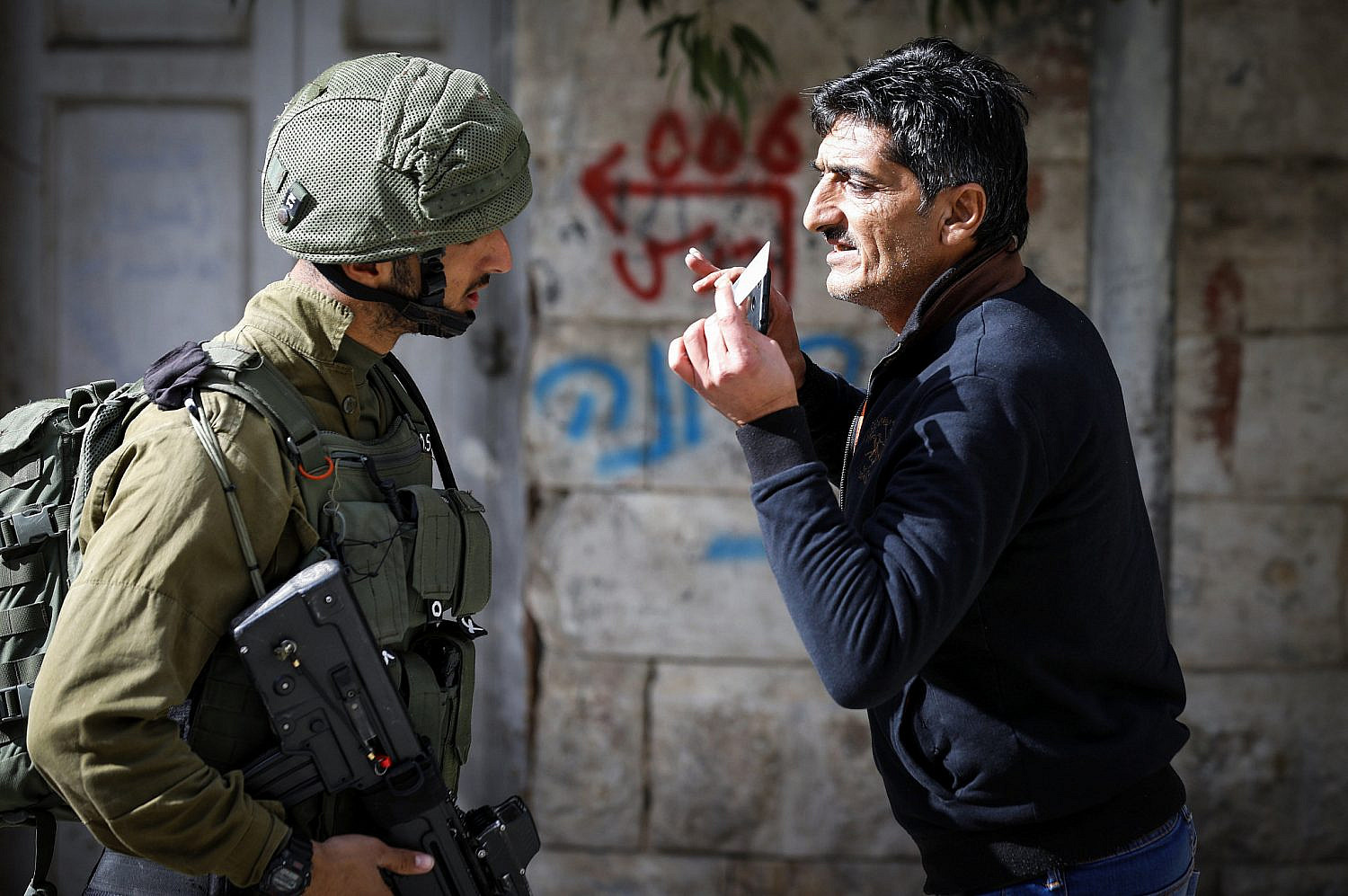 Israeli soldiers speaks with a Palestinian man the Old City of Hebron in the West Bank, Jan. 14, 2018. (Wisam Hashlamoun/Flash90)