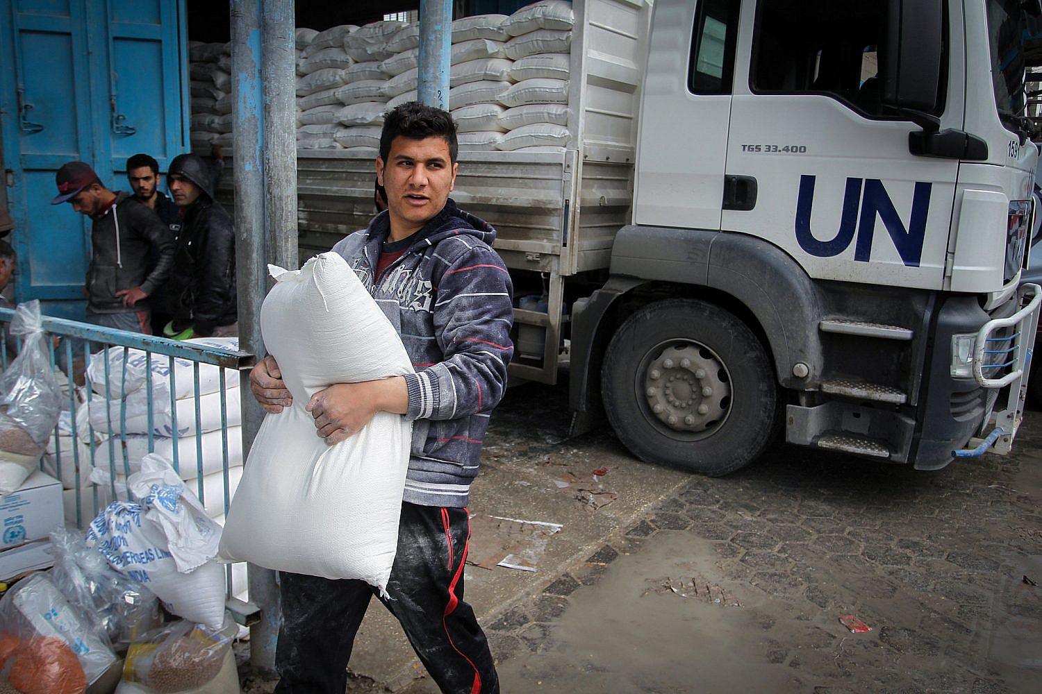 Palestinian refugees collect aid parcels at a United Nations food distribution center in Khan Younis in the southern Gaza Strip, Jan. 28, 2018. (Abed Rahim Khatib/ Flash90)
