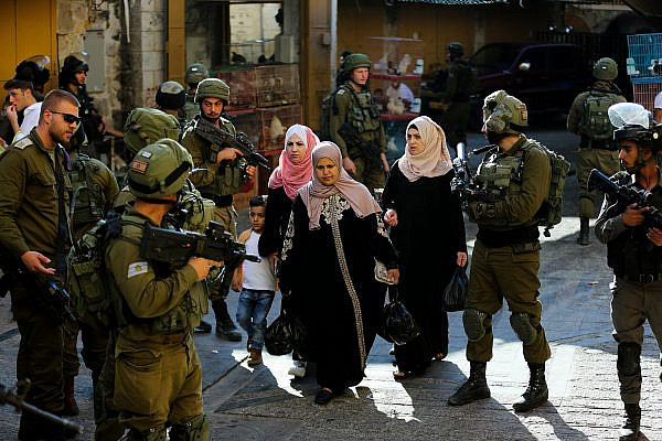Israeli security forces guard as Jews tour the Palestinian side of the Old City Market in the West Bank city of Hebron, June 15, 2019. (Wisam Hashlamoun/Flash90)