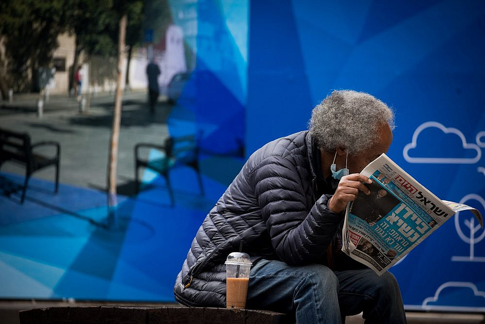 A man wears a face mask and reads newspaper in downtown Jerusalem on Nov. 8, 2020. (Yonatan Sindel/Flash90)
