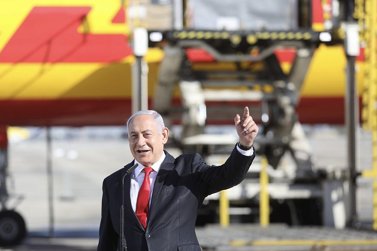 Israeli Prime Minister Benjamin Netanyahu and Health Minister Yuli Edelstein attend the arrival of the DHL freight plane transporting the first batch of Pfizer vaccines landing at Ben Gurion Airport on December 9, 2020. (Marc Israel Sellem/POOL)