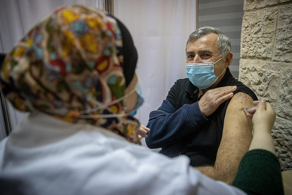 Israelis receive the COVID-19 vaccine at a vaccination center in Jerusalem, on December 24, 2020. (Yonatan Sindel/Flash90)
