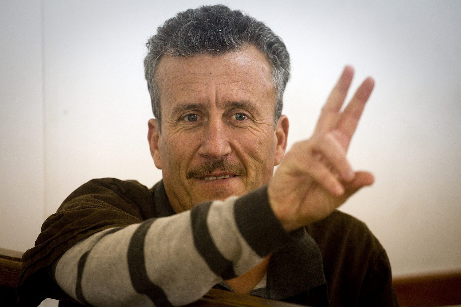 Bassem Tamimi gestures a peace sign during his hearing in an Israeli military court. (Oren Ziv)