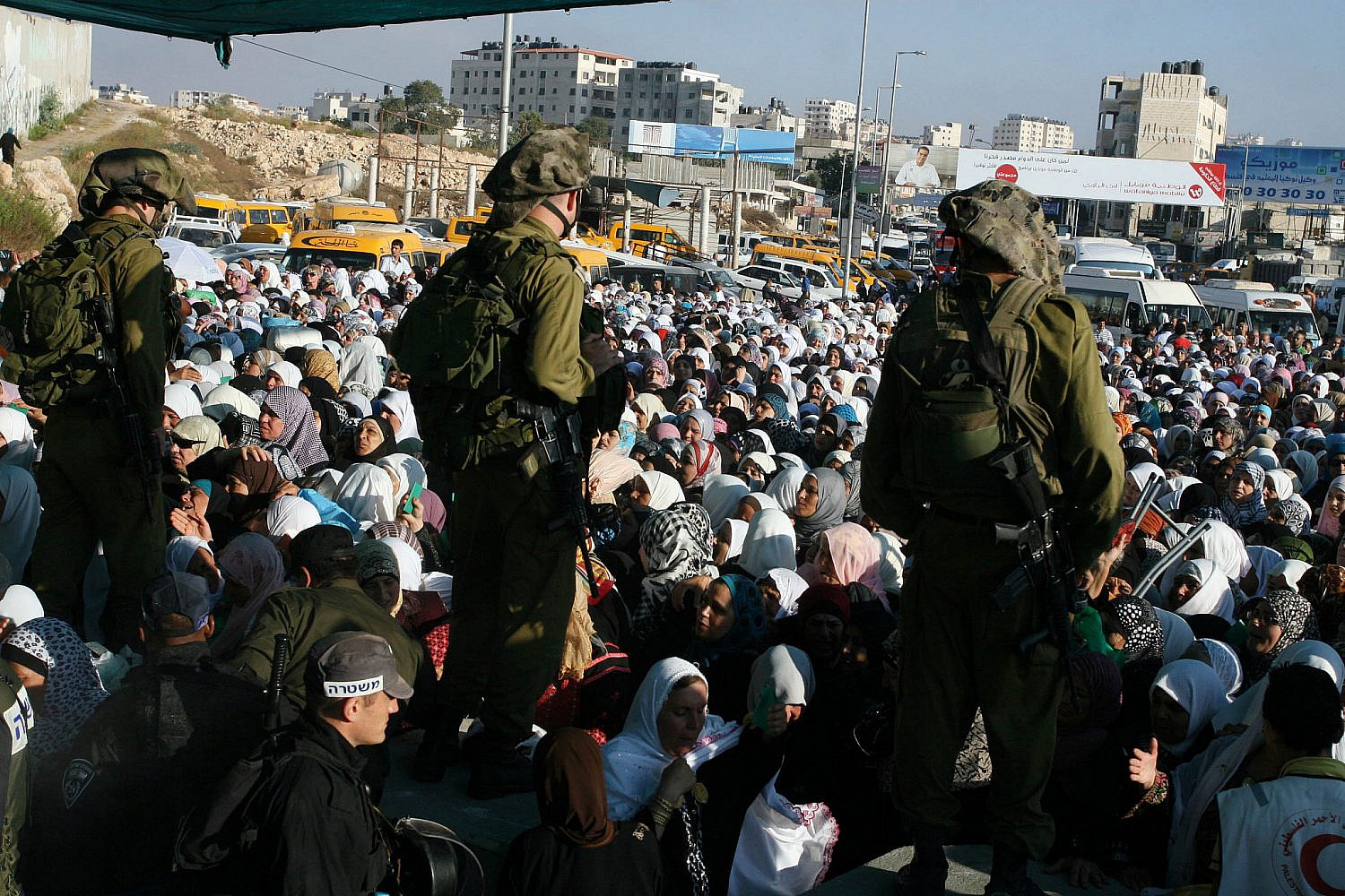 Israeli soldiers checking IDs of Palestinian women as the wait in line to pass the Qalandia checkpoint from Ramallah to Jerusalem, Aug. 19, 2011. (Issam Rimawi/Flash90)