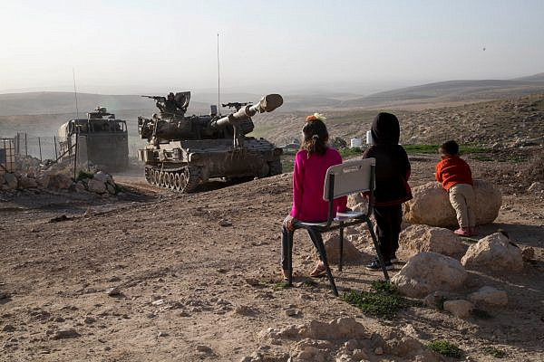 Children in Jinbeh, a Palestinian village in the occupied West Bank, watch as the Israeli army conducts a drill, February 3, 2020. (Keren Manor/Activestill.org)