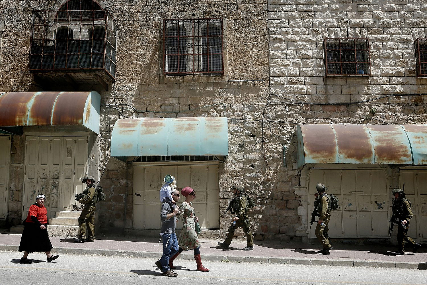 Israeli soldiers patrolling on Shuhada Street in the West bank city of Hebron, as hundreds of Orthodox Jews arrive to pray at the Cave of the Patriarch, during the Jewish holiday of Passover. April 16, 2014. (Miriam Alster/Flash90)
