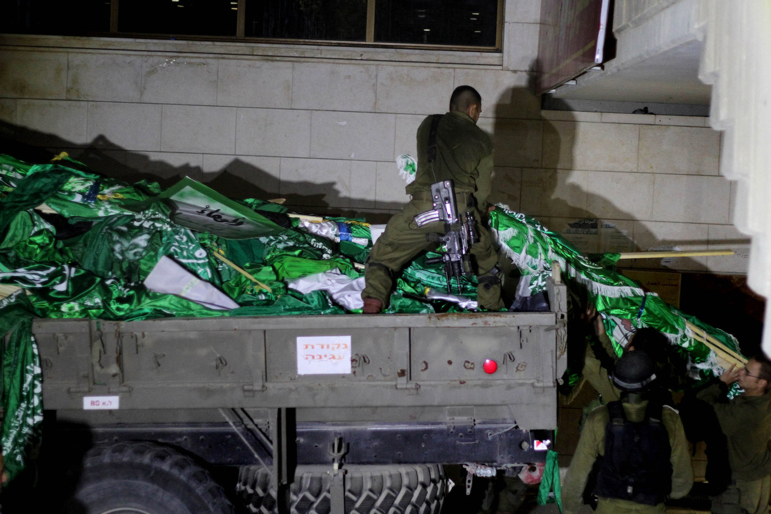 Israeli soldiers seen confiscating Hamas flags during a night raid on Birzeit Univeristy, West Bank, June 19, 2014. (Issam Rimawi/Flash 90)
