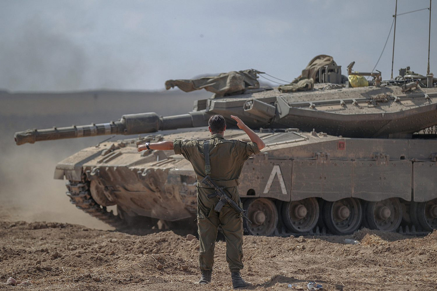 An Israeli soldier directs a Merakva tank after pulling back from the Gaza Strip, Aug. 3, 2014. (Flash90)
