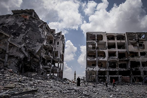 Palestinians walk in front of buildings destroyed by Israeli military forces in the northern Gaza Strip town of Beit Lahiya, Aug. 4, 2014. (Emad Nasser/Flash90)