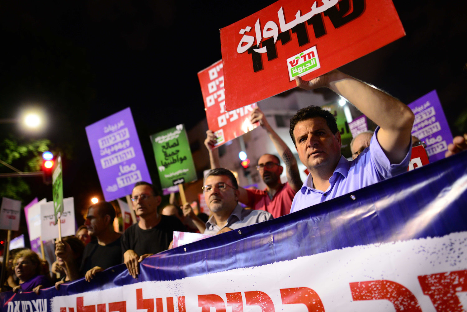Joint List head Ayman Odeh (right), MK Yousef Jabareen (center), and former MK Dov Khenin (left) take part at a protest march against Jewish Nation-State Law, Tel Aviv, July 14, 2018. (Tomer Neuberg/Flash90)
