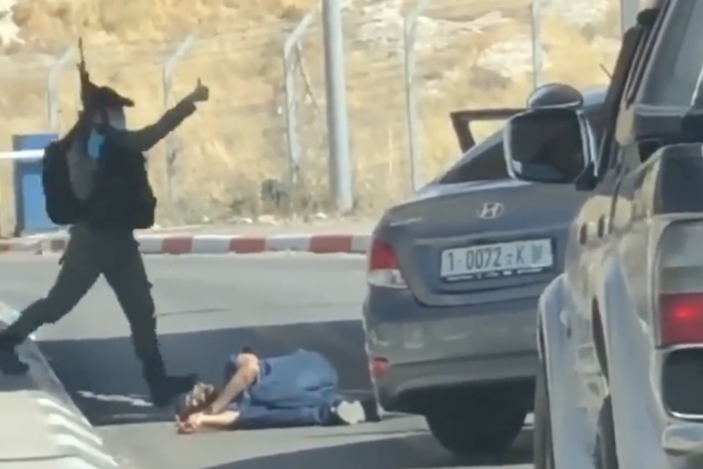 An Israeli Border Police officer gives a thumbs up next to the body of Ahmed Erekat. (Forensic Architecture investigation)