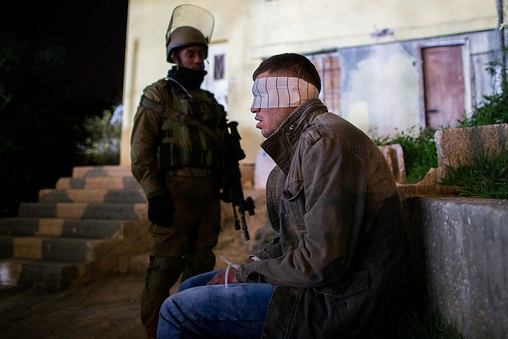 Nachshon Battalion soldiers watch over a Palestinian detainee during an operation of arresting suspects in the Dheisheh Refugee Camp, near the West Bank city of Bethlehem, Dec. 8, 2015. (Nati Shohat/Flash90. )