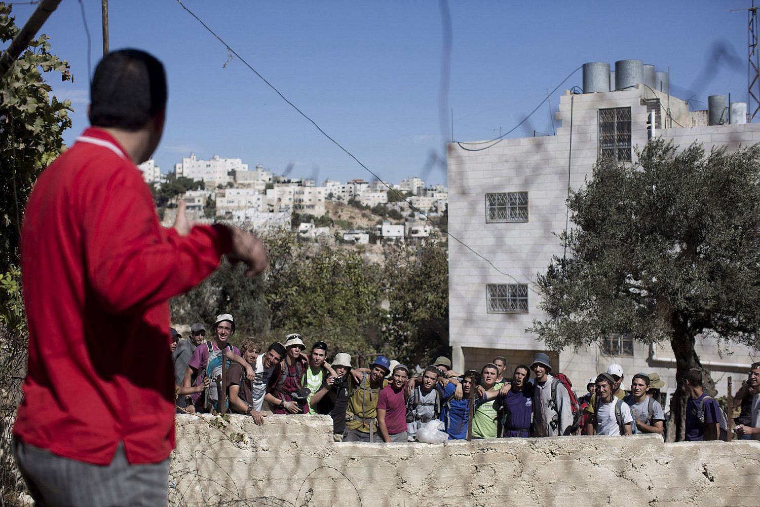"Issa Amro, a coordinator of the group ""Youth Against Settlements,"" looks at Israeli settlers during a tour in the Tel Rumeida neighborhood in the West Bank city of Hebron, October 25, 2013. (Activestills)"