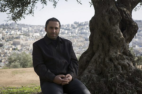 Palestinian activist Issa Amro poses for a photo in the West Bank city of Hebron, December 2, 2014. (Activestills)