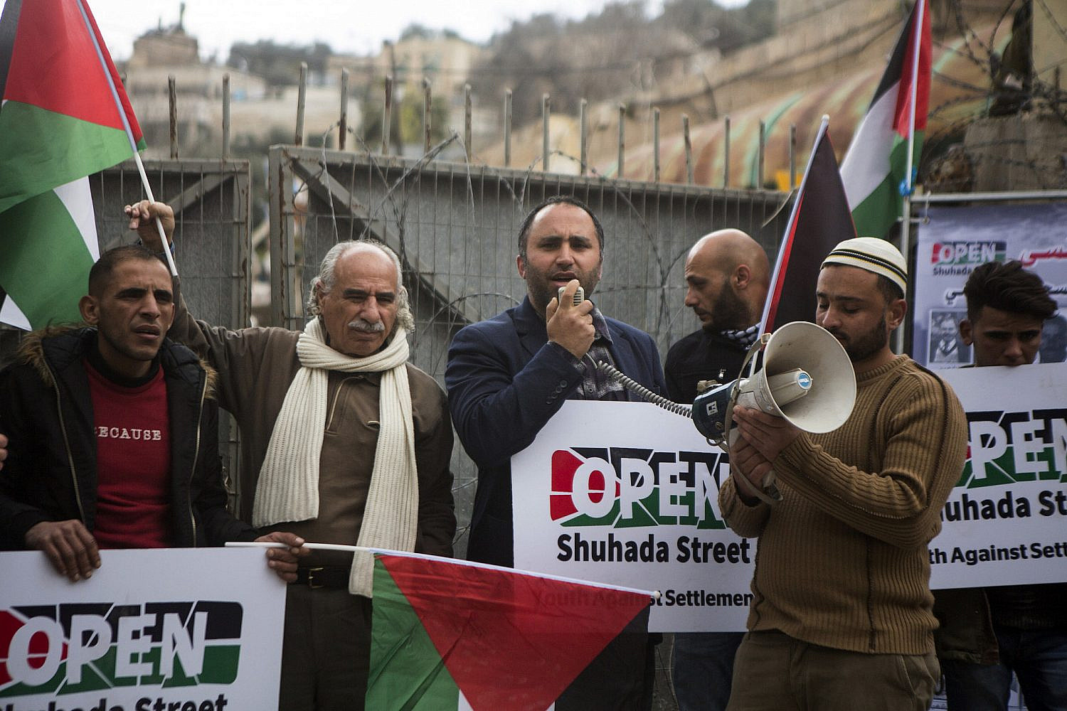 Issa Amro gives a speech during a demonstration commemorating the 1994 Ibrahimi Mosque massacre and calling for the opening of Shuhada Street, Hebron, West Bank, February 20, 2019. (Activestills)
