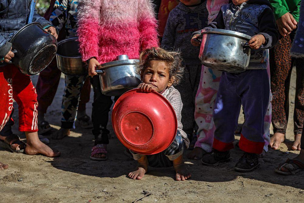 A woman serves food to Palestinian children in Gaza City, Gaza on January 21, 2021. (Mohammed Zaanoun)