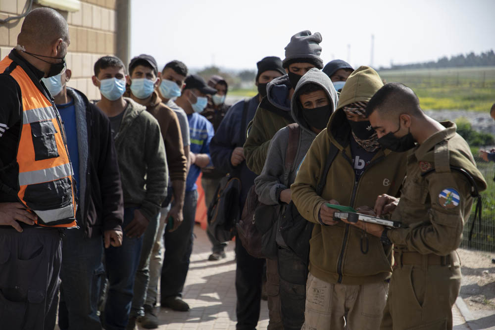 An Israeli soldier registers Palestinian workers to be vaccinated at a makeshift Israeli vaccination site, Metar checkpoint, in the southern West Bank, March 8. (Oren Ziv)