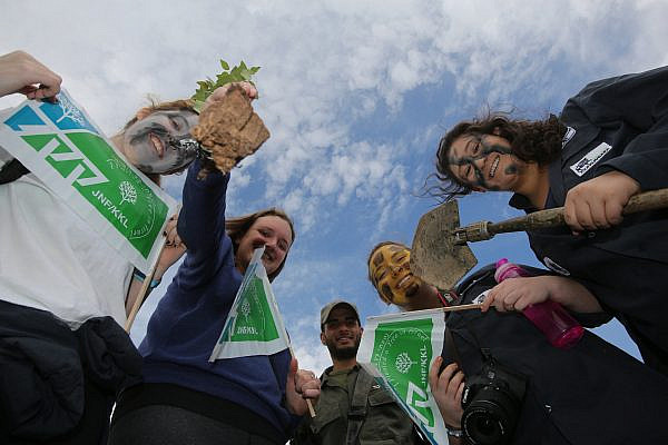 Israelis holding signs of the Jewish National Fund (Keren Kayemeth LeIsrael) take part in a Tu Bishvat tradition of planting trees, in the West Bank Jewish settlement of Michmash, in the Binyamin District, Jan. 15, 2014. (Yossi Zamir/Flash90)