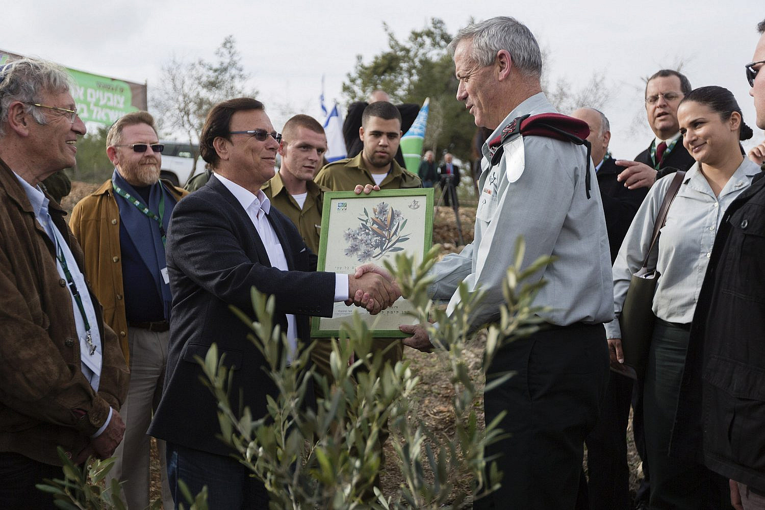 Then-IDF Chief of Staff, Benny Gantz (R), receives a certificate from Chairman of the Jewish National Fund, Effy Shtenzler, after planting a tree at the new General Staff Forum and IDF forest in the Sataf area near Jerusalem, Jan. 27, 2014. (Flash90)