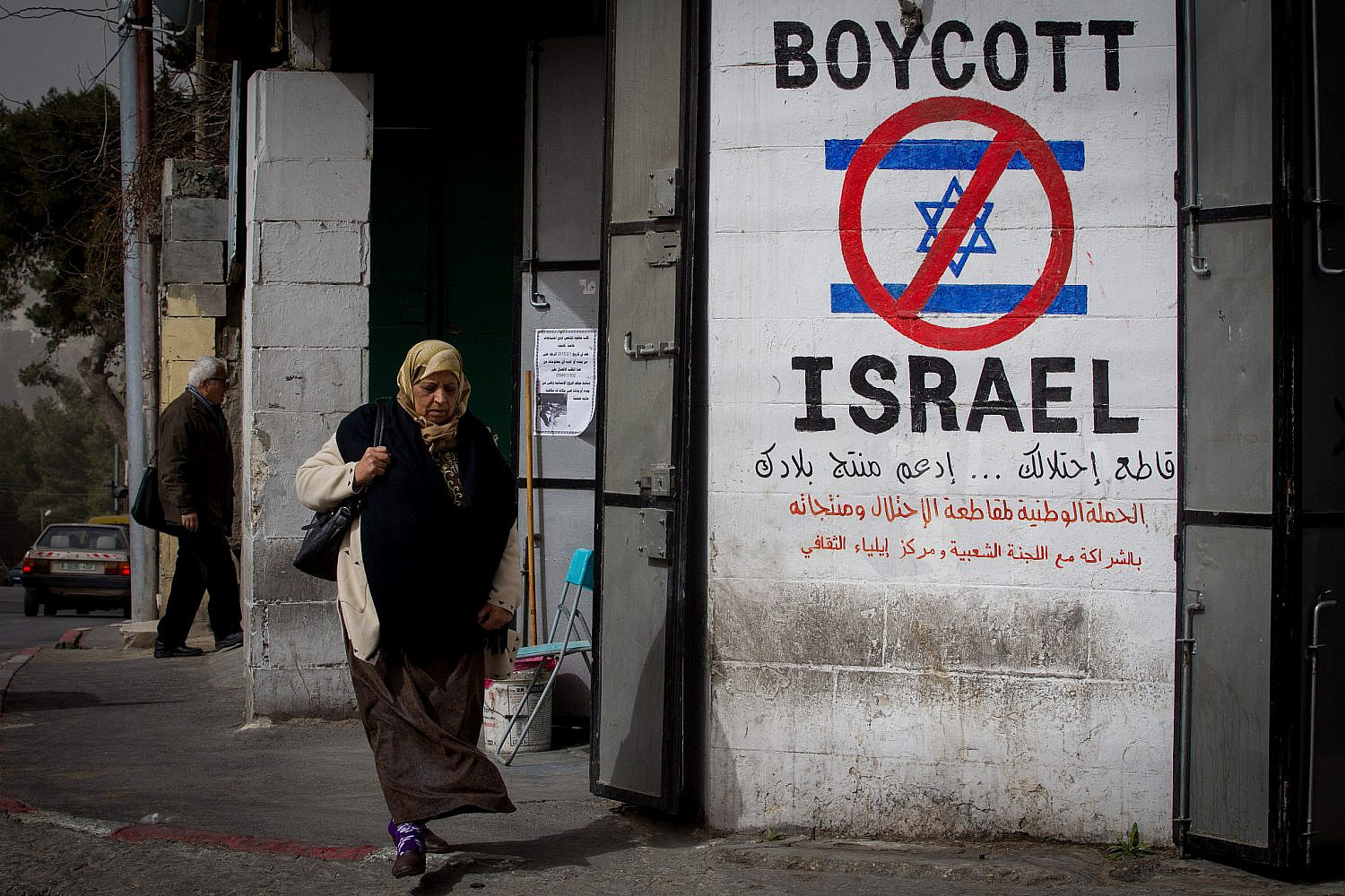 A Palestinian woman walks by a grafitti sign calling to boycott Israel seen on a street in the West Bank city of Bethlehem on February 11, 2015. (Miriam Alster/Flash 90)