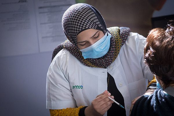 A Palestinian Arab woman gives a COVID-19 vaccine at a vaccination center in Petah Tikva, January 27, 2021. (Miriam Alster/Flash90)