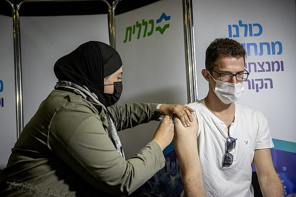 An Israeli receives the COVID-19 vaccine injection at a vaccination center in Jerusalem, February 16, 2021. (Yonatan Sindel/Flash90)