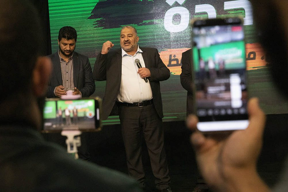 Ra'am leader Mansour Abbas (center) speaks to his supporters on election night in the city of Tamra, March 23, 2021. (Oren Ziv)