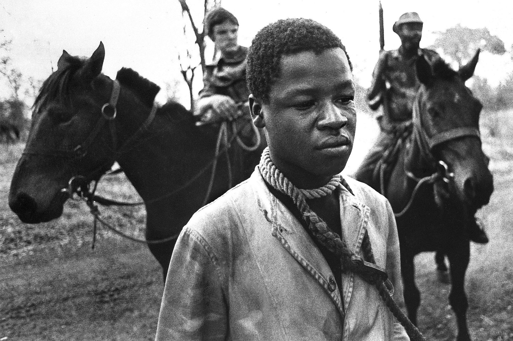 A prisoner taken by Rhodesian Security Forces in the fall of 1977 stands with a rope around his neck. (J. Ross Baughman)