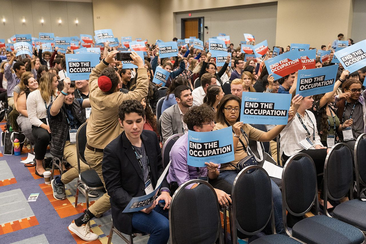 Attendees of the 2019 J Street national conference hold up signs that say