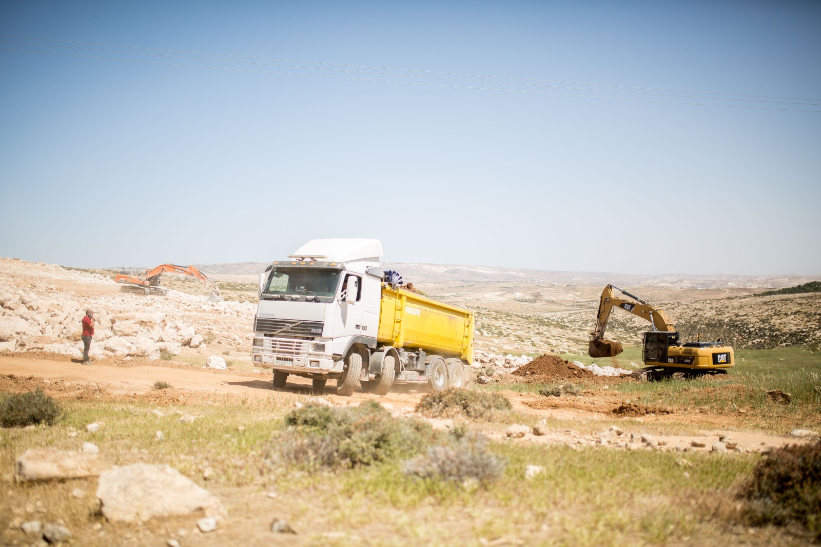 Israeli bulldozers trucking fertile soil from the wadi uphill to the development site in Ein al-Beida, West Bank, April 15, 2021. (Emily Glick)
