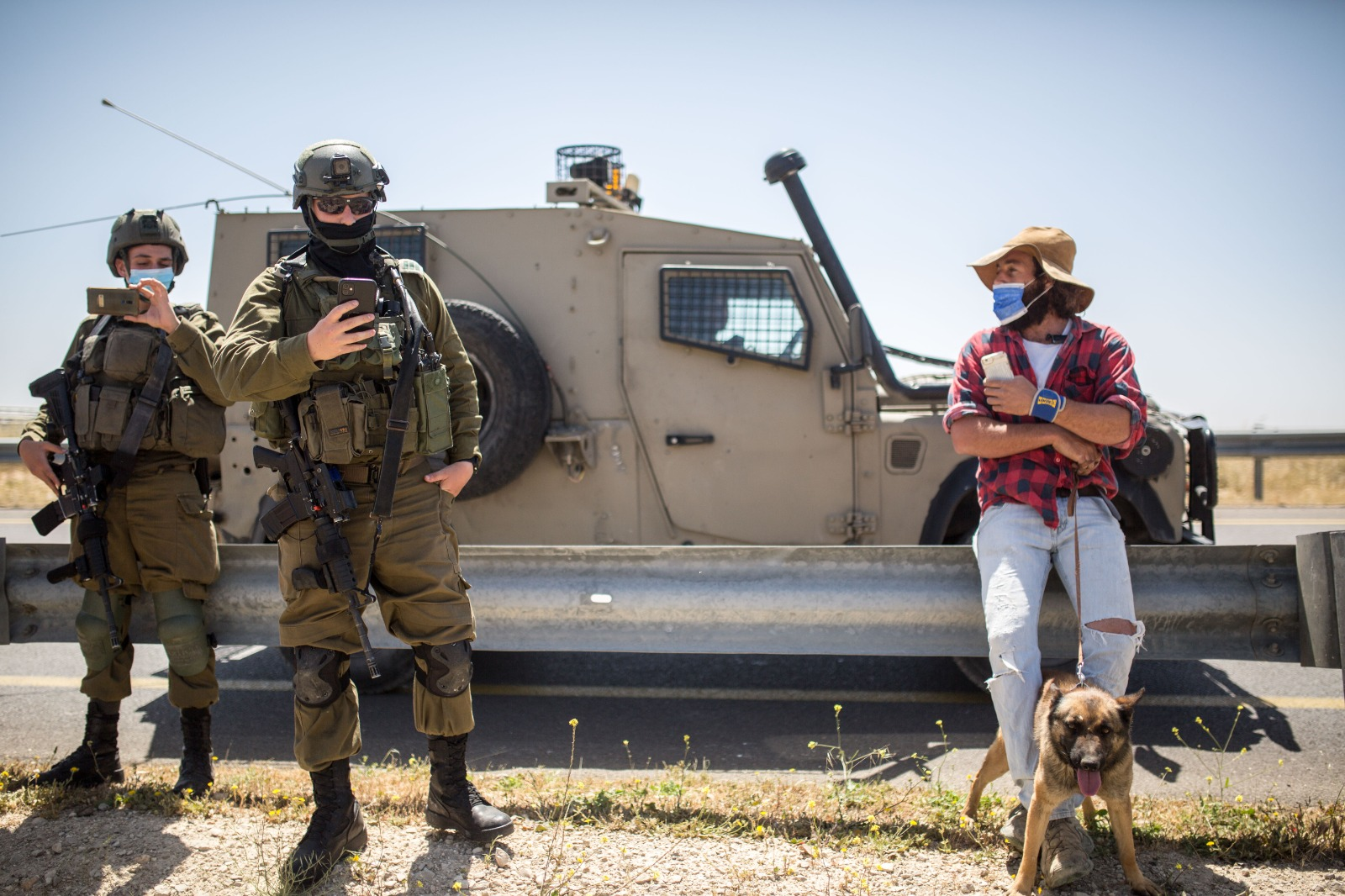 An Israeli settler overseeing the development activities in Ein al-Beida in the West Bank, joined by soldiers during construction, April 15, 2021 (Emily Glick)