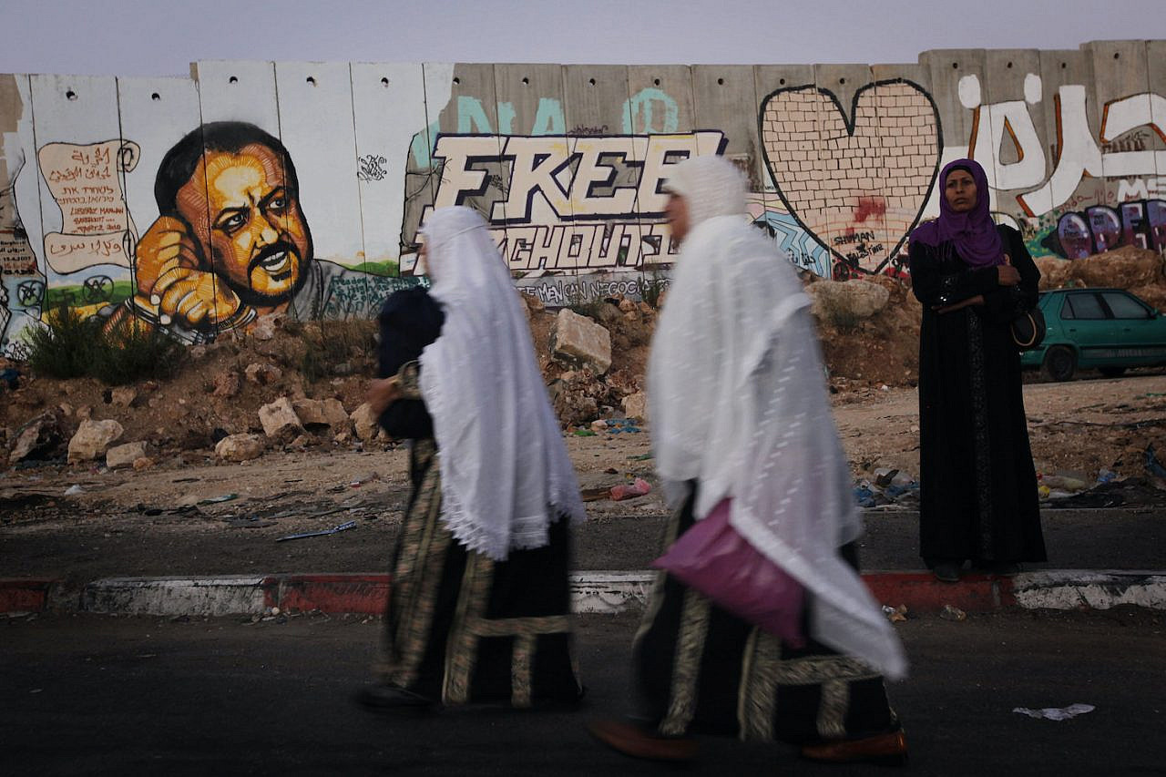 Palestinians pass by a graffiti of the imprisoned Palestinian leader Marwan Barghouti, painted on the Israeli separation wall at the Qalandia checkpoint near Ramallah, September 3, 2010. (Miriam Alster/Flash90)