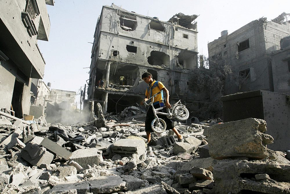 A young Palestinian boy walks among the debris of a house, which witnesses said was hit in an Israeli air strike, in Rafah, southern Gaza Strip, Aug. 2, 2014. (Abed Rahim Khatib/Flash90)