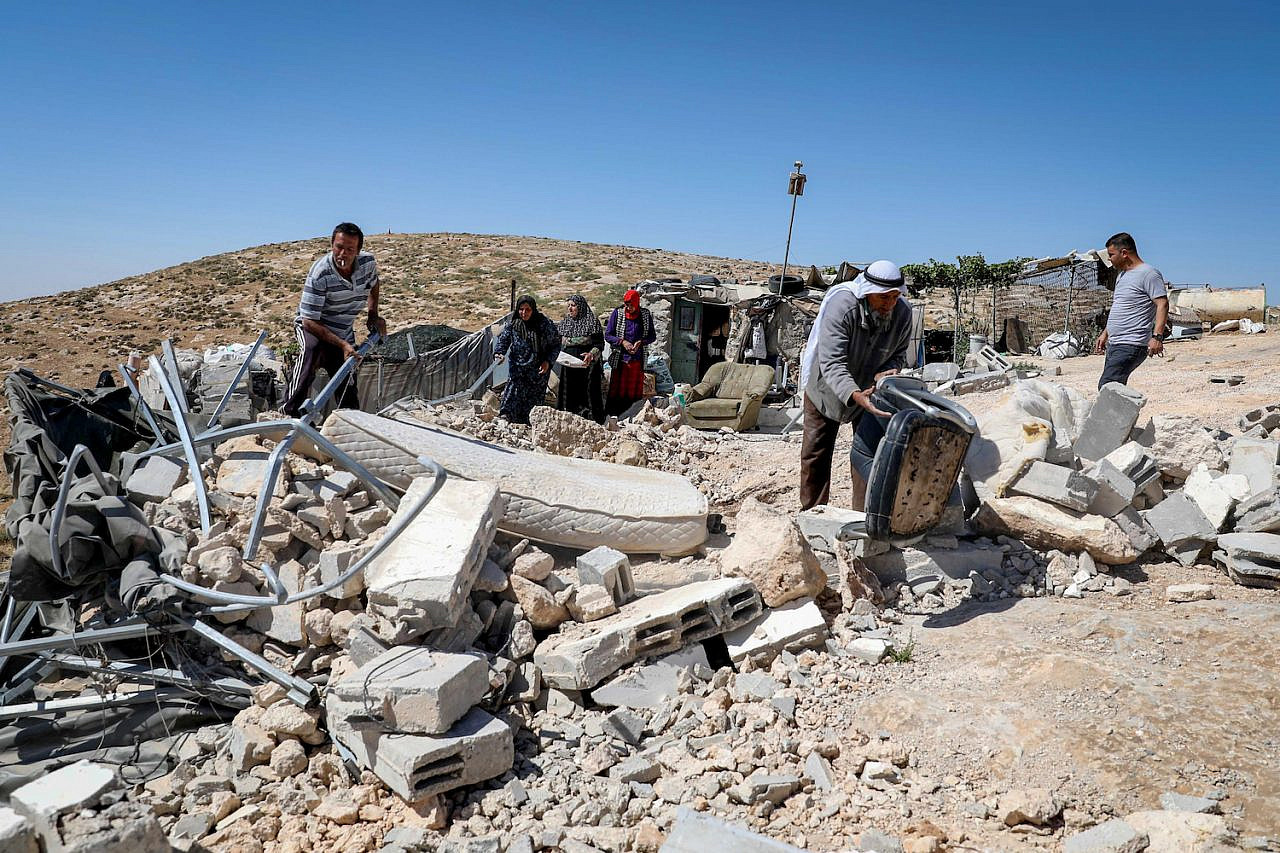 Palestinians collect their belongings after Israeli forces demolished their house in the occupied West Bank city of Yatta, south of Hebron, June 3, 2020. (Wisam Hashlamoun/Flash90)
