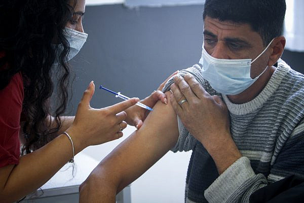 Palestinians working in Israel receive a COVID-19 vaccine, south of Tulkarm in the West Bank on March 8, 2021. (Nasser Ishtayeh/Flash90)