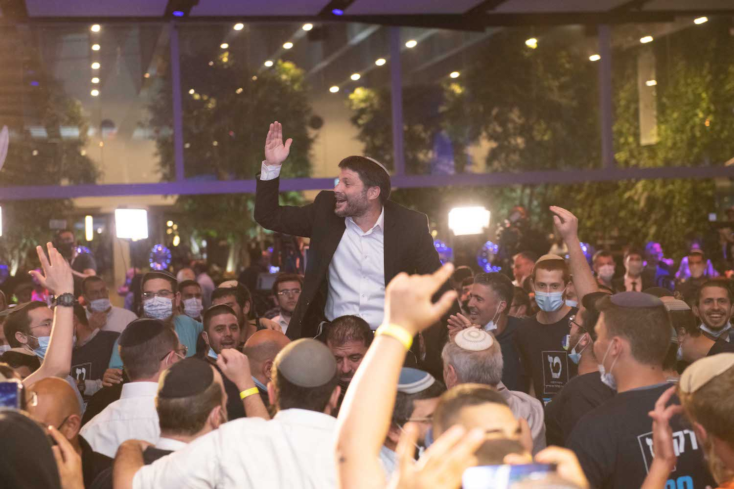 Head of the Religious Zionist Party Bezalel Smotrich is hoisted up by supporters at the party headquarters in Modi'in on election night, March 23, 2021. (Sraya Diamant/Flash90)
