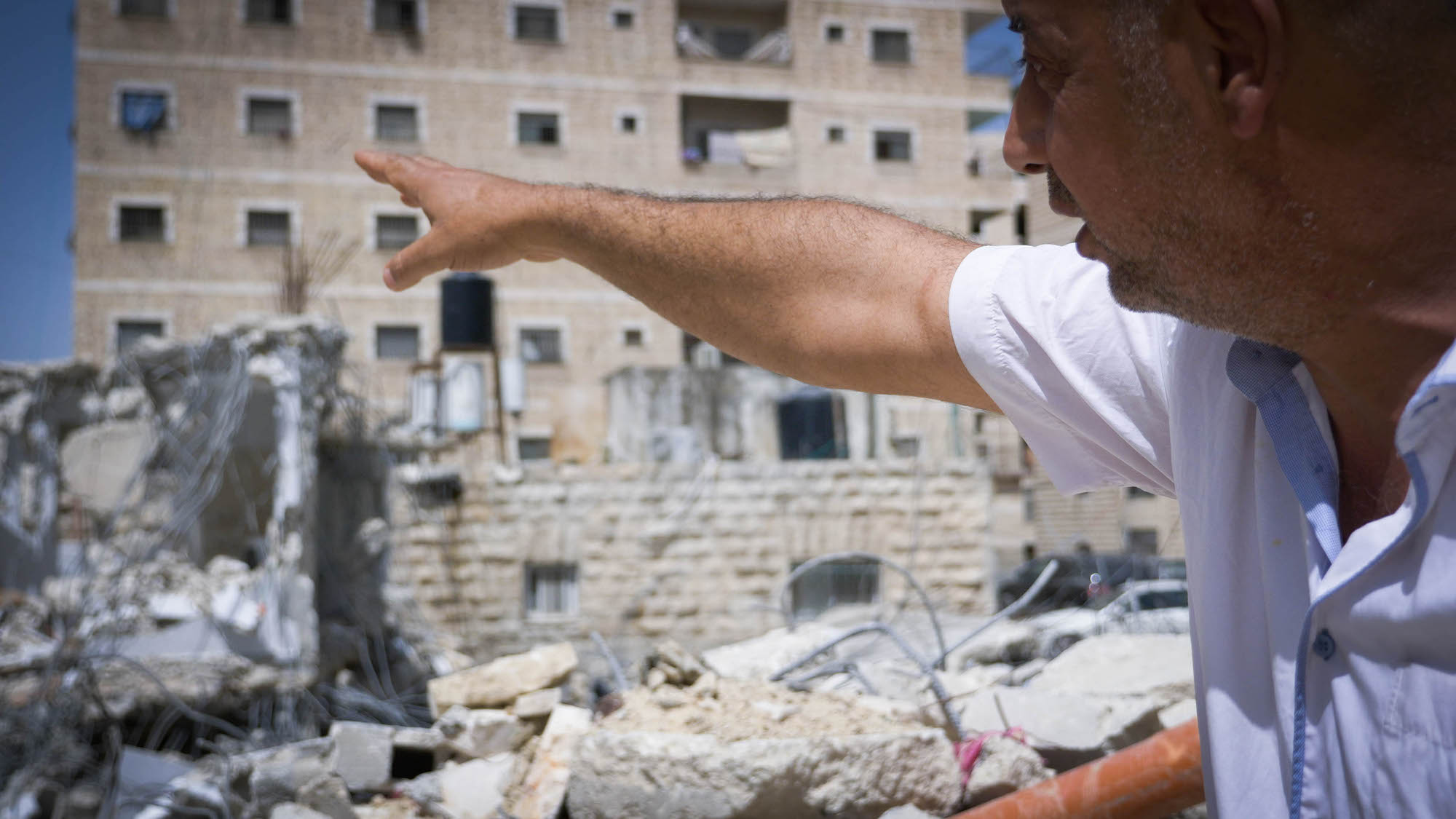 Ihab Hassan Ali stands on the remains of his family home in Shuafat Refugee Camp, East Jerusalem. (Rachel Shor)